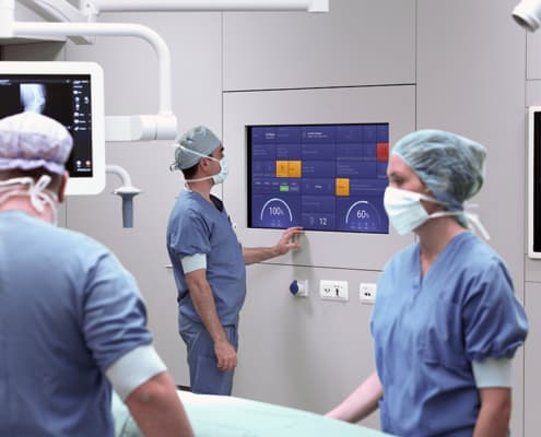 Three surgeons working in the OR around our OR dashboard